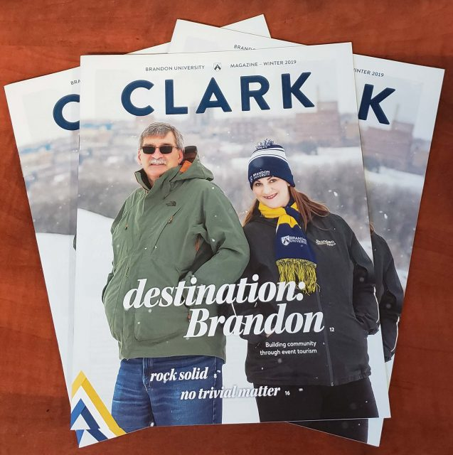 Cover of Clark Magazine features a man and woman standing on a snowy hill, overlooking a city skyline