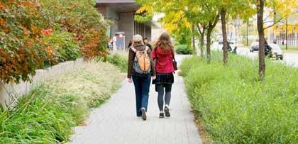 Two female students walking on sidewalk.