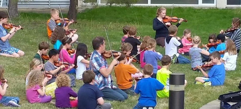 A class playing violins outside on grass
