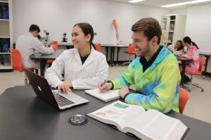 Pair of students laughing in lab