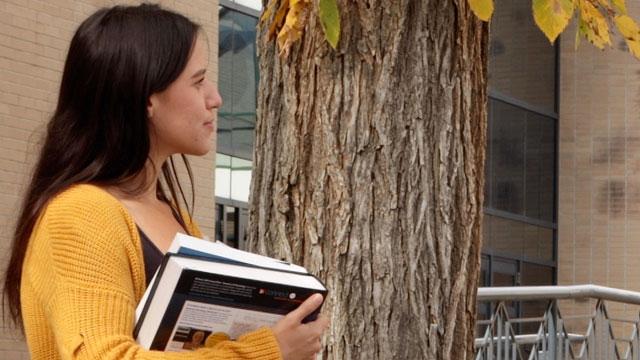 Female student holding textbooks