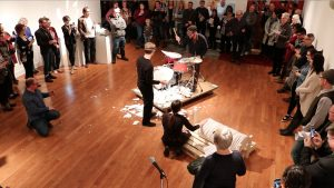 A man sits at a drumset at the centre of a room and hits porcelain discs while surrounded by observers. Another man stands beside the drumset waiting to present him with the next porcelain disc.