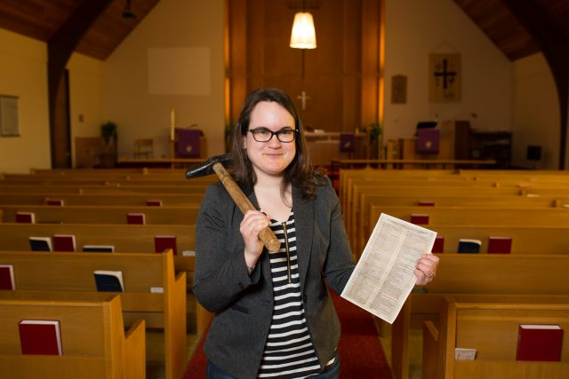 A woman poses in a church with a hammer over her shoulder while holding a historical document.