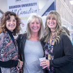 Three women smile for the camera in front of banners in the Healthy Living Centre