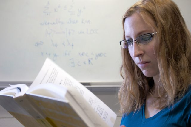 Sarah Plosker reads a book while standing in front of a white board with equations written on it