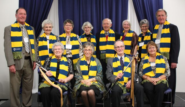 Four men and eight women pose in two rows wearing blue and yellow scarves. A woman and a man seated in the front row are holding the Senior Stick and the Lady Stick - black staffs with silver heads and ribbons hanging from close to the heads.