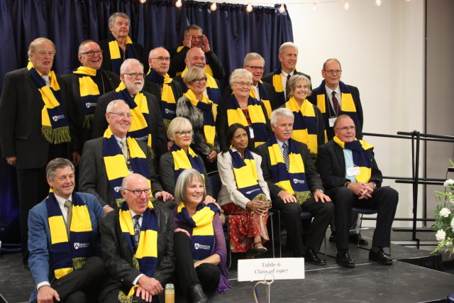 A large group of people pose on stage wearing blue and gold BU scarves