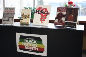 A book case displays a Black History Month sign, with a number of books on top.