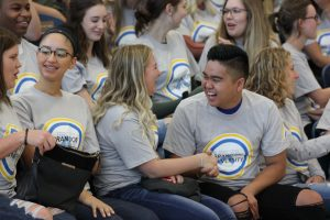 Two students smile and laugh as they shake hands while seated among a large group of students