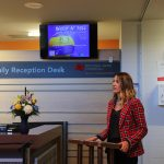 A woman stands at a podium and speaks. A sign behind her reads Auriat Family Reception Desk and also contains the logo of National Bank Financial.