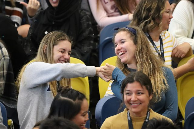 "Two women, surrounded by other smiling students, laugh as they twist their arms while ""thumb wrestling"""