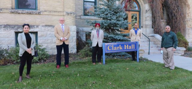 A women and four men stand, spaced apart, in front of a building. Between the second and third men is a sign that says Clark Hall