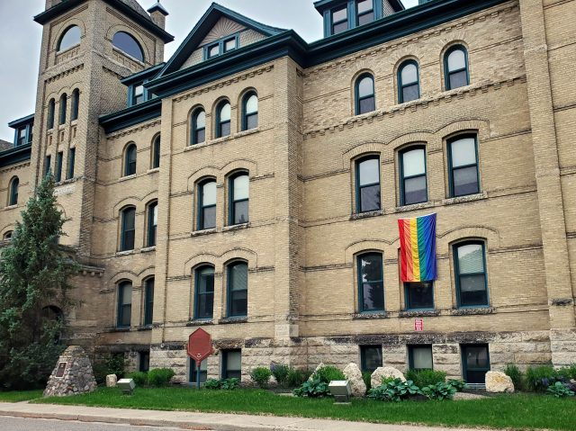 A building has a rainbow flag displayed on the front