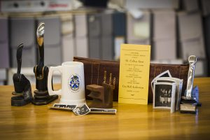Several itesm, including stamps, a coffee cup, a book and photographs sit on a table