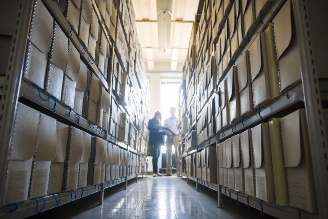 A pair of people are seen, obscured by light shining behind them, at the end of a long row with shelves filled with folders