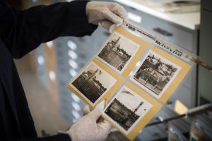 A pair of gloved hands hold a sheet that contains four black-and-white photographs