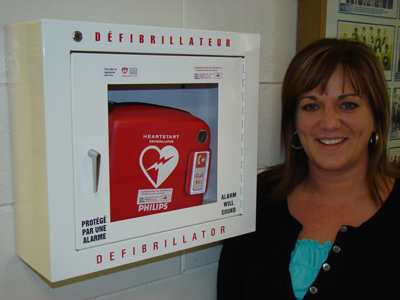 Corrie Farguson from the Physical & Health Education Department stands next to the new AED in the BU gymnasium.
