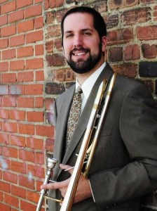 Aaron Wilson leans against a brick wall while holding a trombone.