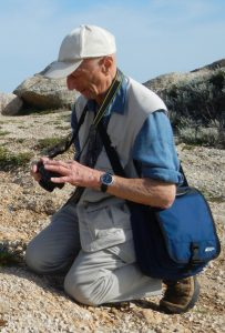 Al Rogosin kneels and photographs a plant while in a rocky area.