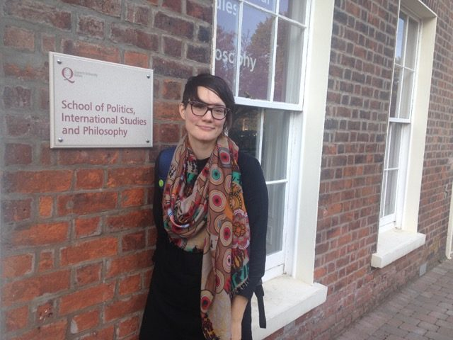 Dr. Allison McCulloch leans against a wall at Queen's University Belfast