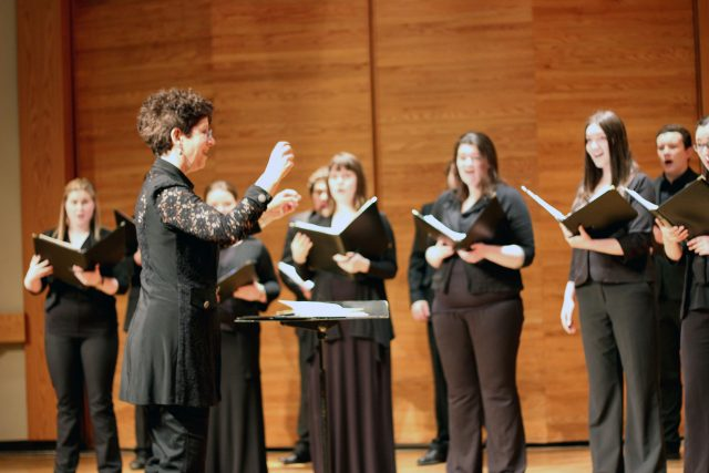 A women is seen from the side as she directs a choir