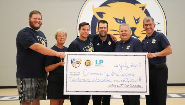 Check presentation participants hold an oversized cheque as they stand in front of a wall that features the BU Bobcats logo