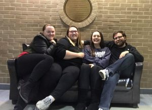 Four students sit on a couch in front of a brick wall.