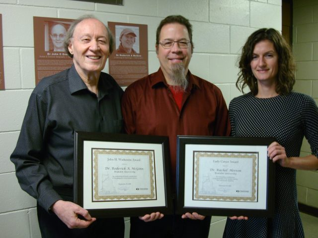 Two men stand in the left and centre of the photo, with a woman on the right. They are holding two framed certificates.