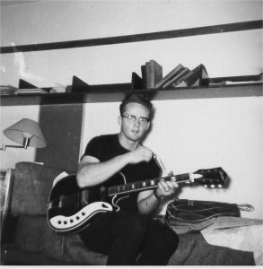Vintage, black-and-white photo of a man sitting on a chair playing an electric guitar