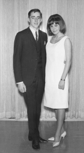 A man in a suit and a woman in a dress stand in front of a curtain in a vintage black-and-white photo