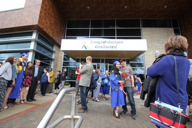 "Graduating students and supporters take photos and mingle in front of the Healthy Living Centre. A sign on the building reads ""Congratulations Graduates"""