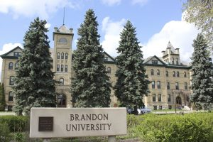 Historic Clark Hall and the Brandon College original building, with a 'Brandon University' sign in front.