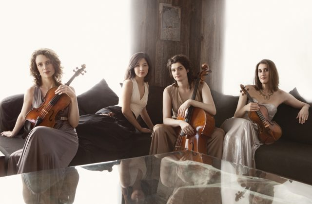 Members of the Cecilia quartet sit on a sofa in front the glowing light of a window, holding their instruments