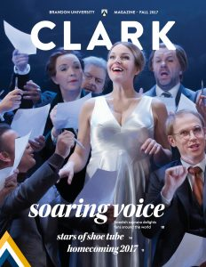 Cover of Clark Magazine, features a photo of opera singer performing onstage surrounded by castmates