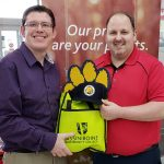 Two men hold a yellow Assiniboine Community College bag and a Brandon University Bobcats hat