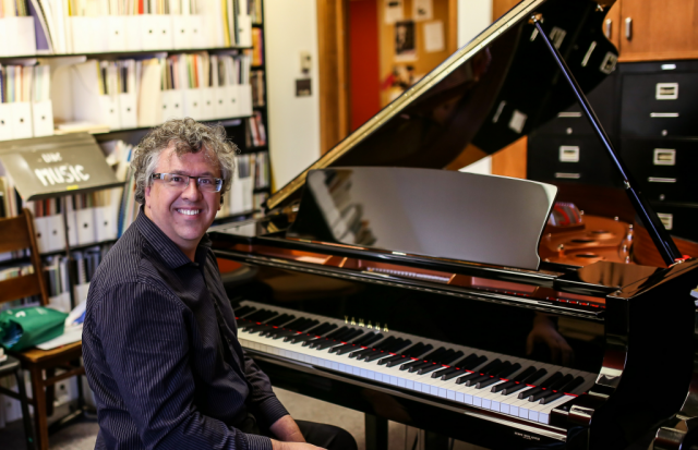 A man is turned to the camera and smiling as he sits at a piano