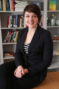 Corinne Mason sits on a desk and smiles for the camera with shelves of books in the background