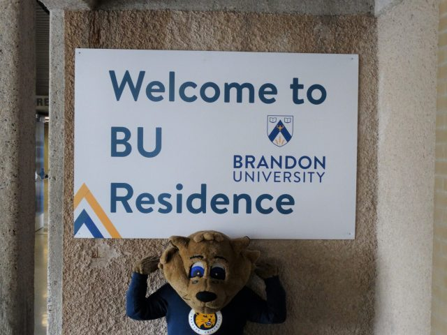 """The BU Bobcat mascot stands under a sign that says """"Welcome to BU Residence"""""""