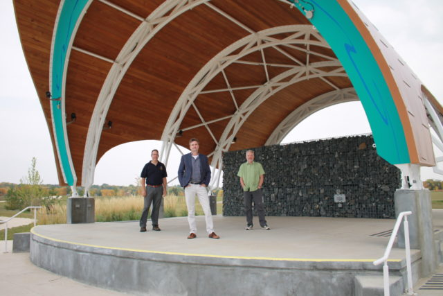 Three men stand on an outdoor stage under a bandstand