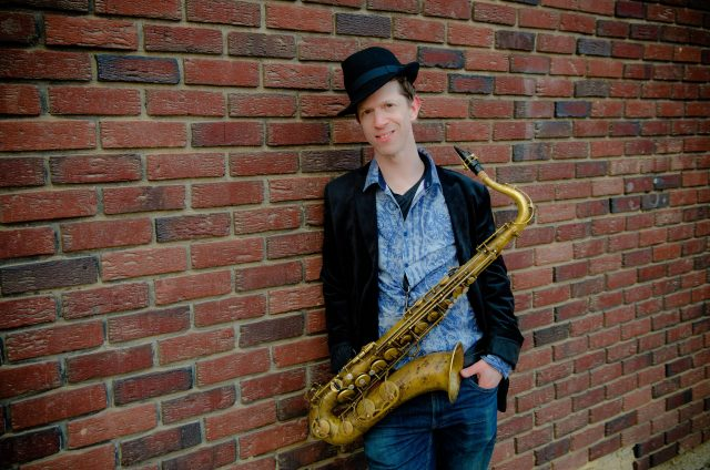 A man leans against a brick wall with a saxophone hanging from his neck