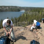 Students work on a rocky hill overlooking a body of water