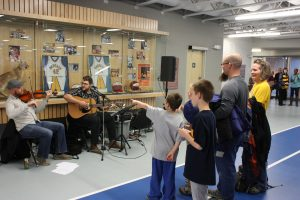A family watches a fiddler and a guitarist perform in front of the Sports Wall of Fame in the Healthy Living Centre