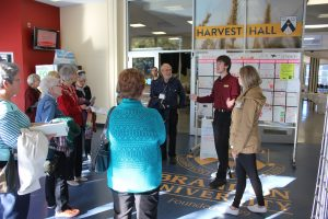A student is surrounded by a group of tour participants as they stand in front of the entrance to Harvest Hall