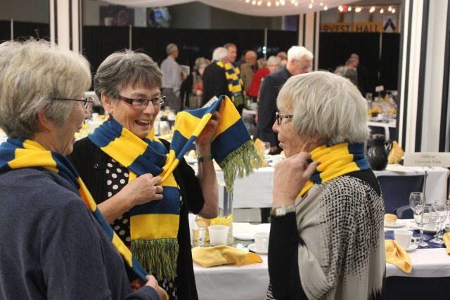 Three women wearing blue and gold striped BU scarves smile and chat