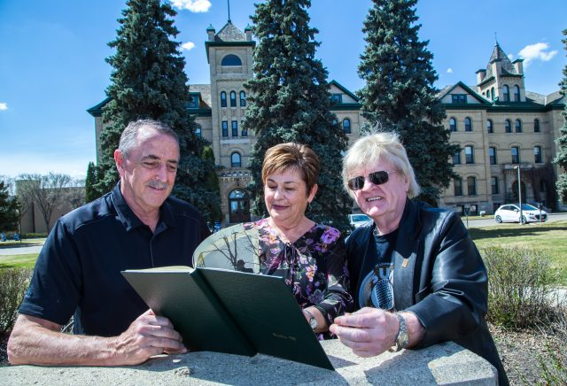 Three people lean on a stone sign and look at a Class of 1968 yearbook in front of Clark Hall