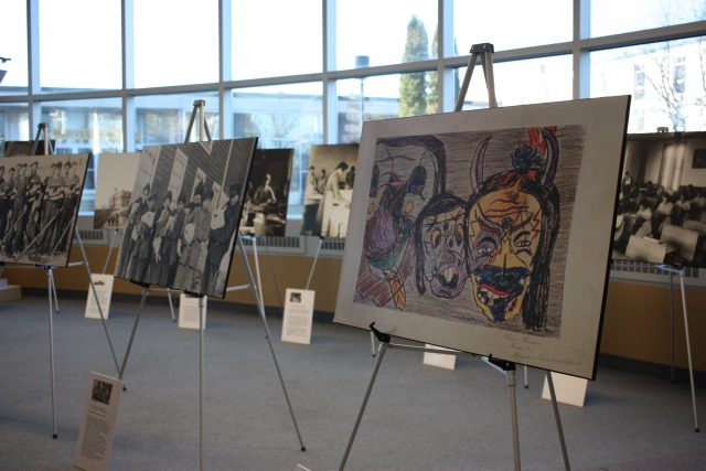 Two rows of easels display images, with the nearest one displaying artwork.