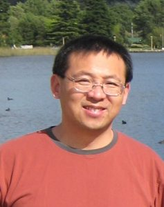 Dr. Li stands in front of a body of water