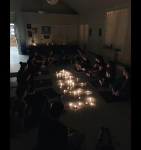 A group of people sit in a circle in a dark room, with candles on the floor in the middle
