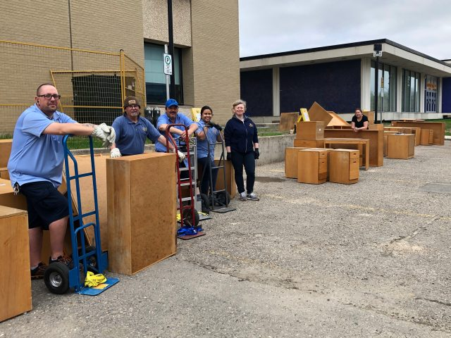 A row of people stand in a parking lost beside a building with pieces of furniture