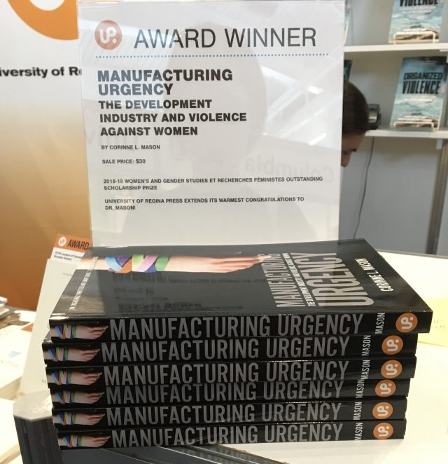 "A pile of books sits underneath a sign with ""Award Winner"" written on top."